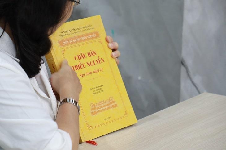 """Bác sĩ Nguyễn Thị Vân Anh cầm trên tay cuốn """"Châu Bản Triều Nguyễn"""" - cuốn sách quý ghi chép nhiều công thức bào chế thuốc của Thái Y Viện"""