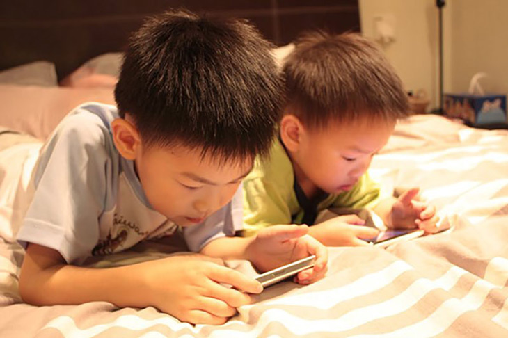 Cho trẻ chơi điện thoại là một trong những nguyên nhân khiến trẻ khó ngủ