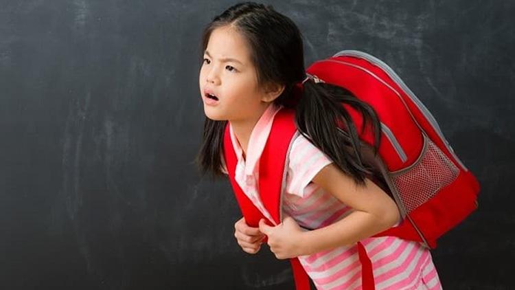 Trẻ đeo balo nặng khiến cột sống chịu áp lực lớn dẫn đến tổn thương và gây thoát vị đĩa đệm