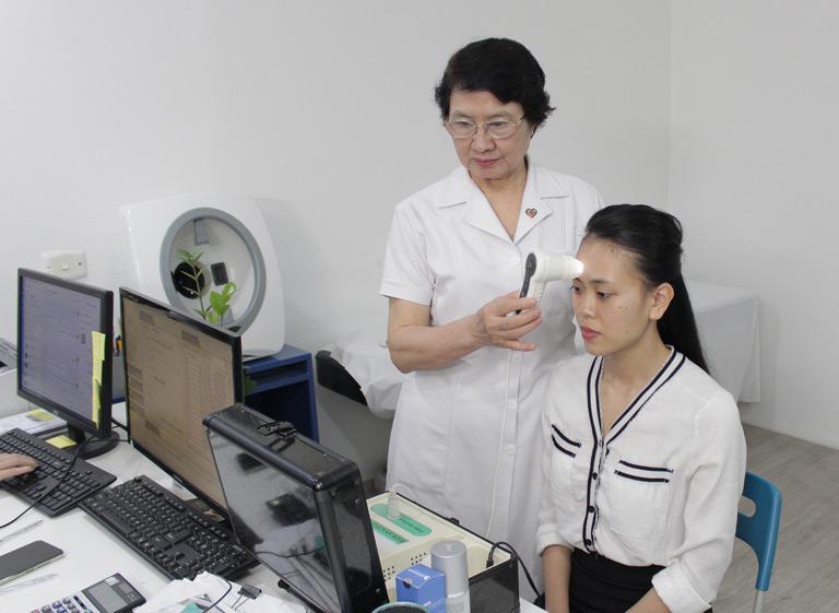 Bác sĩ Nhuần soi da và tư vấn cho chị Trang phương pháp trị mụn phù hợp